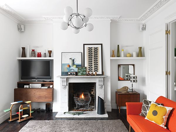 Orla Kiely new living room - floating shelves in alcoves beside fireplace (above TV level, below uplighters)