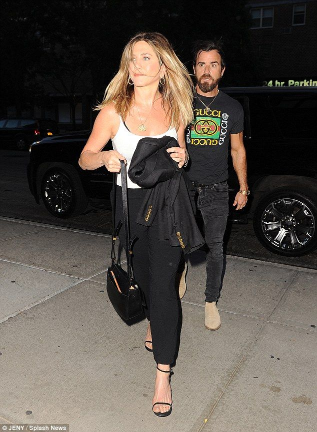 In hiding: Last week the blonde covered her tummy with her jacket when out with husband Justin Theroux in NYC, where they have been spending their early summer