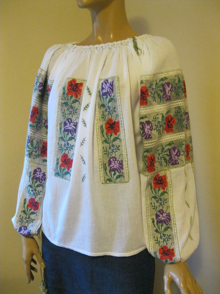 Antique, over 70 - 80 years old Romanian traditional blouse hand embroidered with multi colored cotton thread on homespun traditional fabric. It is completely restored. The antique cross stitch hand embroidery was hand sew on a new gauze cotton. So the result is a new blouse with antique embroideries applied by hand on it. For sale at www.greatblouses.com