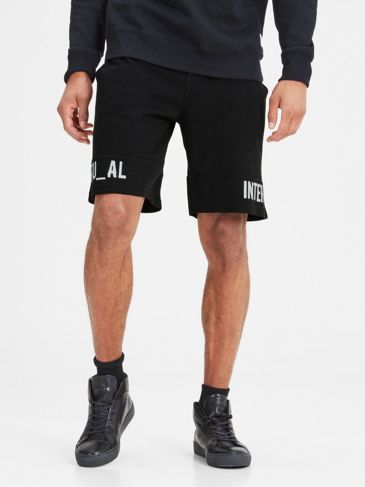 Casual comfort fit short black sweatpants with white graphic print on the sides. Perfect to relax with friends, hang out at home or hit the gym | JACK & JONES