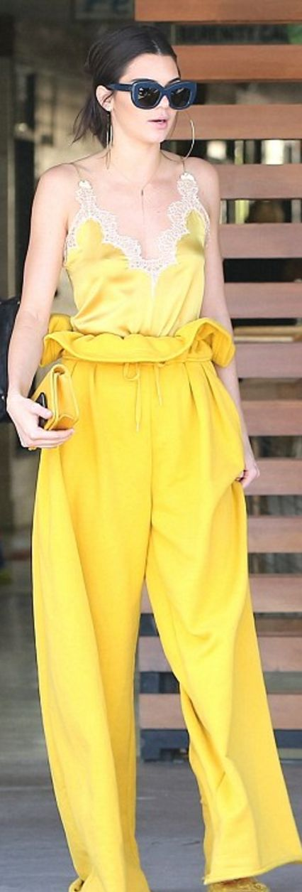 Who made  Kendall Jenner's lace tank top, blue sunglasses, quilted handbag, and yellow pants?