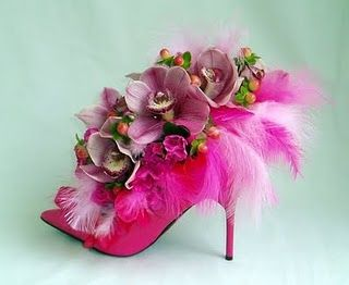 pink shoes filled with flowers for centerpieces, what a great idea! Placed on a mirror for Guest Tables