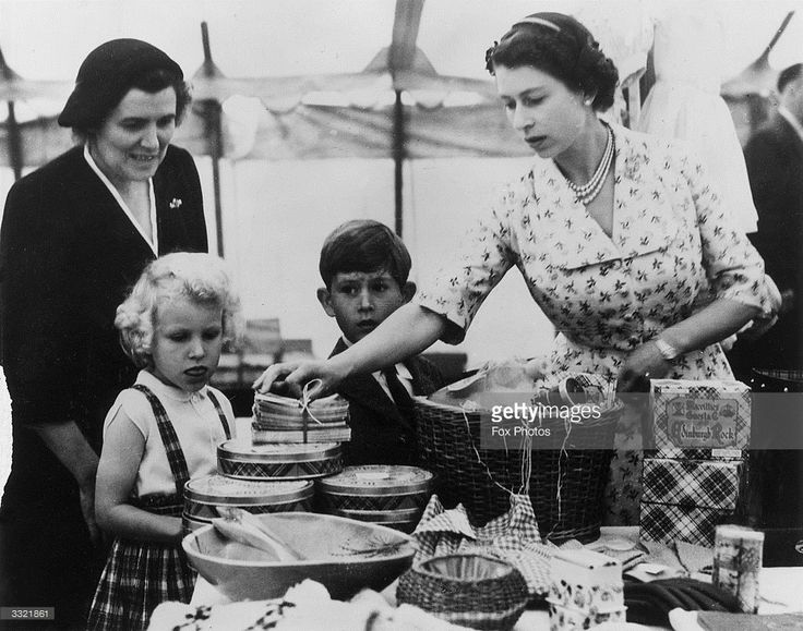 Queen Elizabeth II with Princess Anne, Prince Charles and their nurse, Helen Lightbody, at a stall during a Sale of Work event in Abergeldie Castle, near Balmoral Castle in Aberdeenshire. They are raising funds for the building of a new vestry at Craithie Church.
