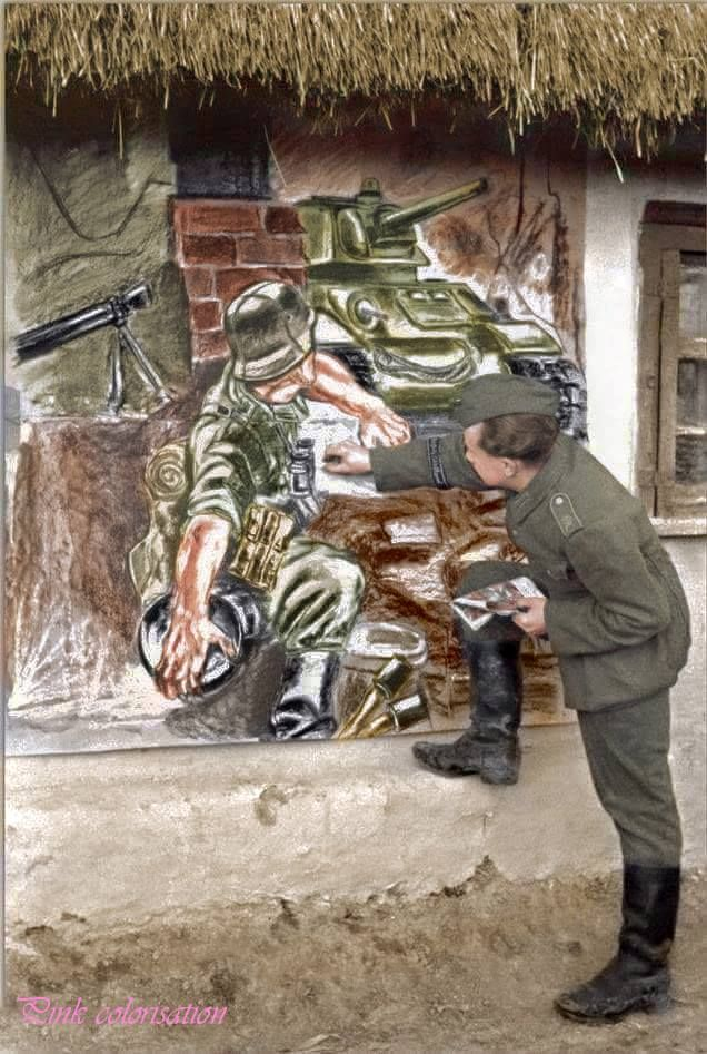 """German soldier from the emblematic Wehrmacht division """"Grossdeutschland"""" drawing a fight scene on a wall."""