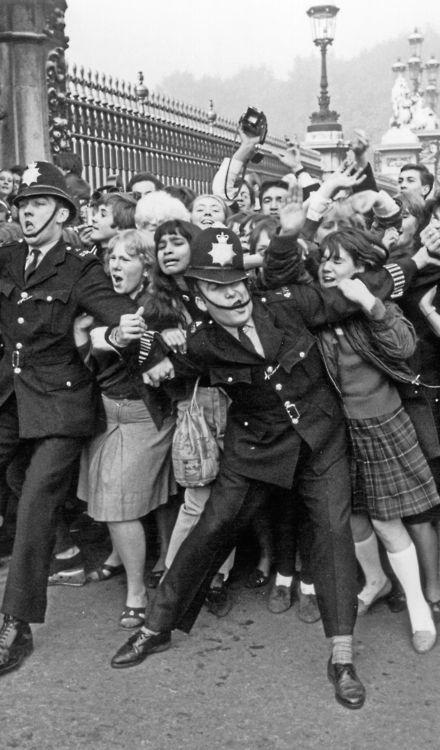 Police struggling to restrain Beatles fans  outside Buckingham Palace [October 1965]