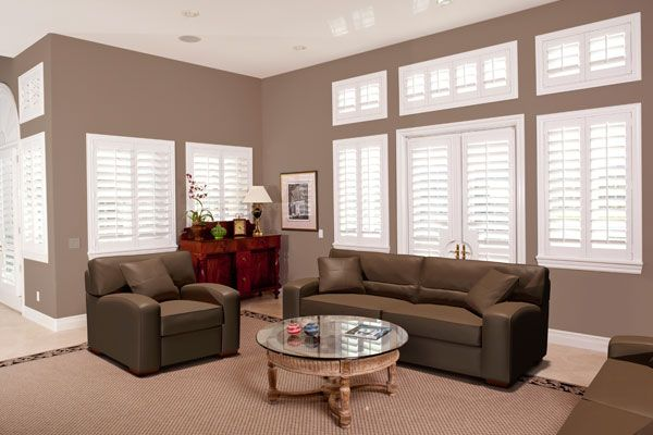White plantation shutters in a dark tan living room with a brown leather couch