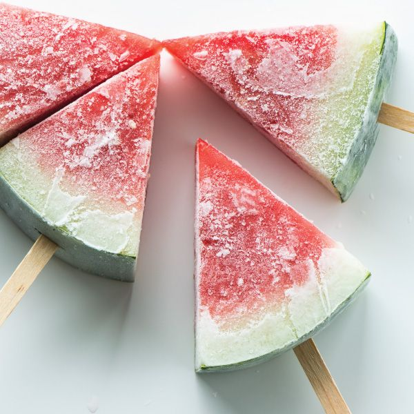 A healthy frozen treat by simply sticking popsicle sticks in watermelon wedges and freezing them.