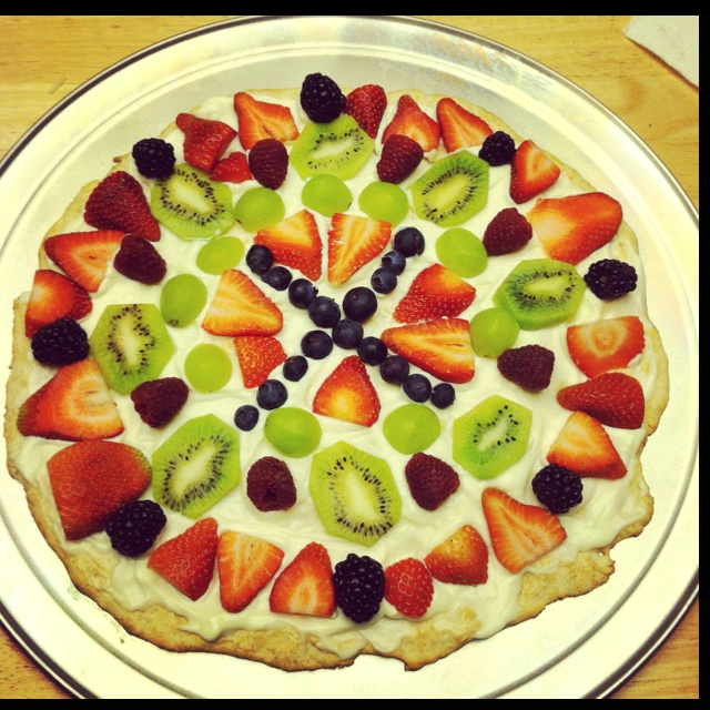Fruit Pizza.. Lighter recipe. This fruit pizza recipe tastes great! Some fruit pizza recipes are made on cookie dough and covered with even more sugar... But this one uses a homemade thin pizza crust instead.      Topping the baked crust, we have a balanced, sweet, and creamy sauce that will lay between the fruit toppings and the pizza crust. Using the recipe link posted above, I tweaked my pizza just a little bit.