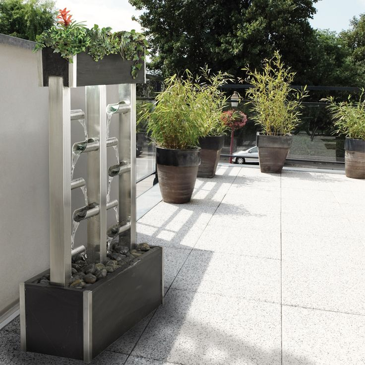 """Cactose's """"Orchis"""" fountain (réf. 103666LEX) made of natural slate and stainless steel, with a plant tray above."""