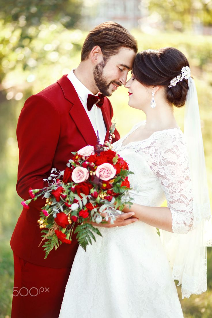 Bride and groom embracing, wedding couple, dark red color marsala style design. Suit with maroon bow - Marsala wedding couple, bride and groom embracing, dark red color style design. Suit with maroon bow tie, white dress, bridal bouquet. Professional makeup. Eternal love, tenderness, beauty concept.