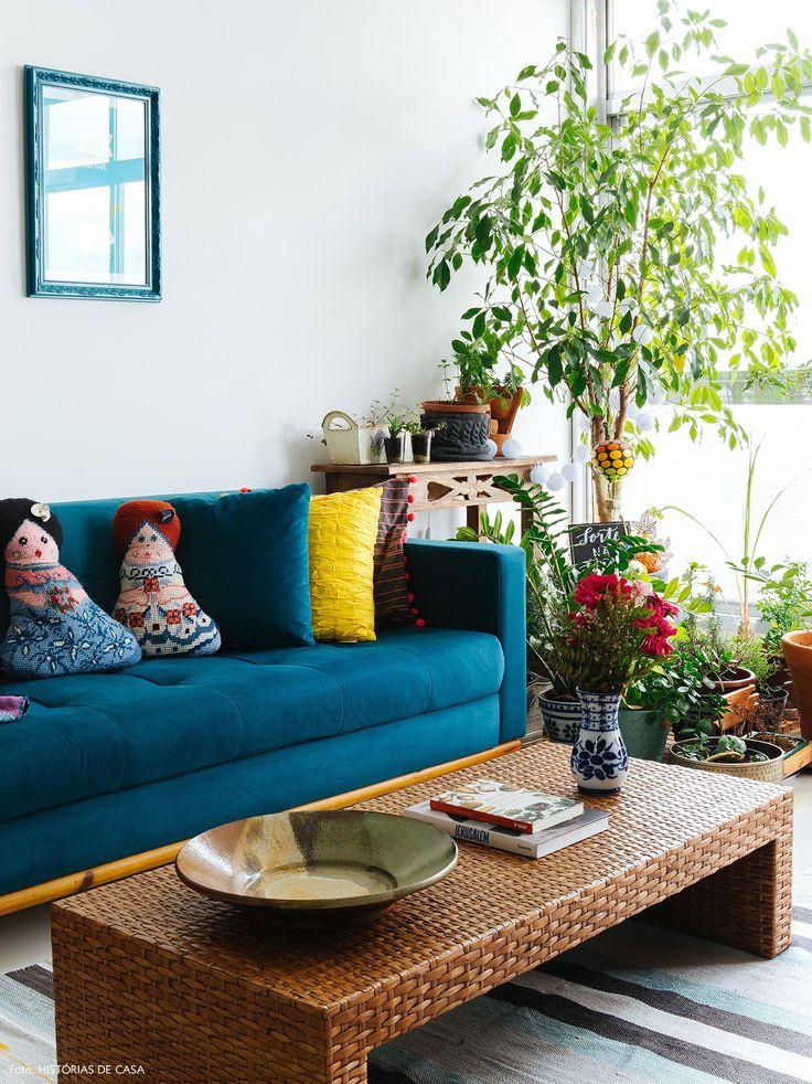 Sala de Estar tem sofá azul, tapete kilim, mesa de fibras naturais e muitas plantas.