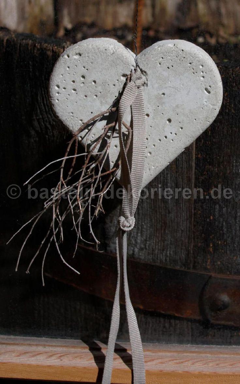 Herz aus Beton mit einem Satinband und einem kleinen Ästchen dekoriert.