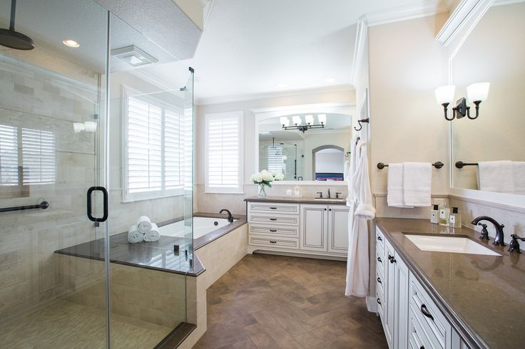Coordinating the Caesarstone Wild Rice quartz with the espresso-glazed cream cabinets gave this room contrast with a sense of relaxation for these busy home owners. Various sizes of honed Crema Marfil Marble fill the shower walls including a border detail and mosaic at the shower floor. Wood tile flooring set in a herringbone pattern was created to both be inviting as well as add texture balancing the space.