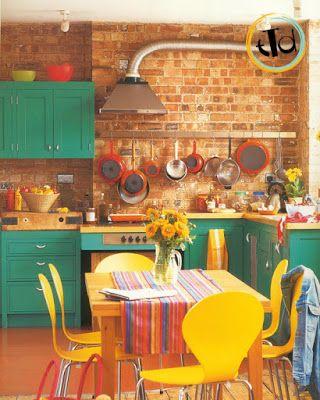 cucina che mantiene la parete in mattoni originale e accosta le sedie gialle ad un mobile color verde menta davvero particolare!