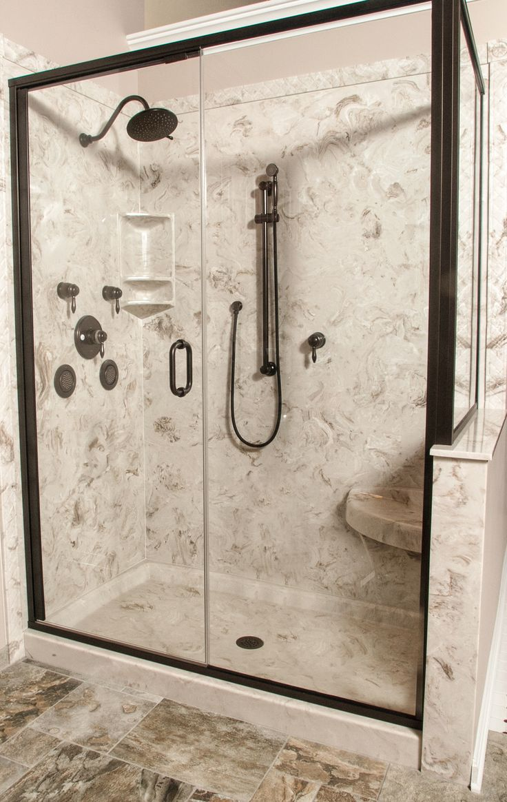 """Cultured marble shower with corner seat, decorative-edge trim with 3 tiered corner shower caddy. Moen thermostatic shower with handheld on slide bar. 8"""" rain shower head in oil-rubbed bronze. Semi-frameless oil-rubbed bronze hinged shower door."""