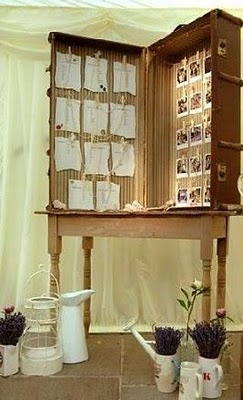 Escort cards and engagement photos displayed in vinatge suitcase