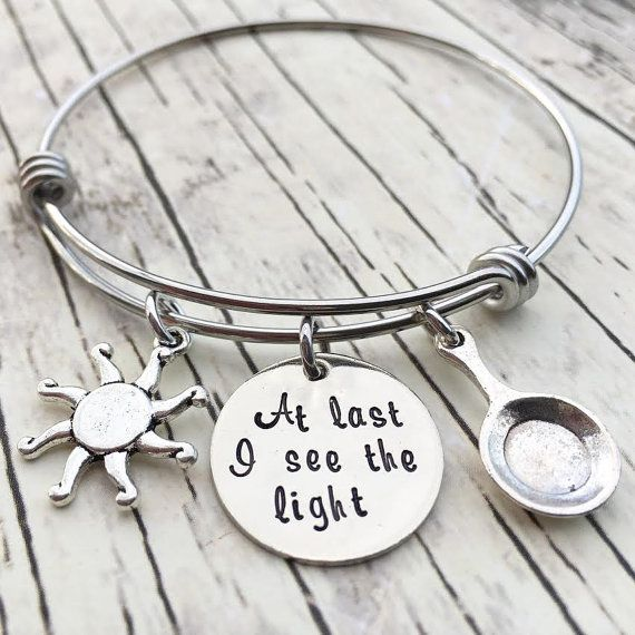 OUR STORY: At KK&Whimsy, we love incorporating personalized elements into our style! We know that each of our clients have a unique story and have walked a unique journey that ultimately created who they are at their core. Our hand stamped jewelry is a tribute to your life, your family and all the things you love. ITEM DESCRIPTION: This Tangled bangle is made of a 3/4, 20 gauge nickel disc and is hand stamped with the phrase At last I see the light. It is coupled with a Tibetan Silv...