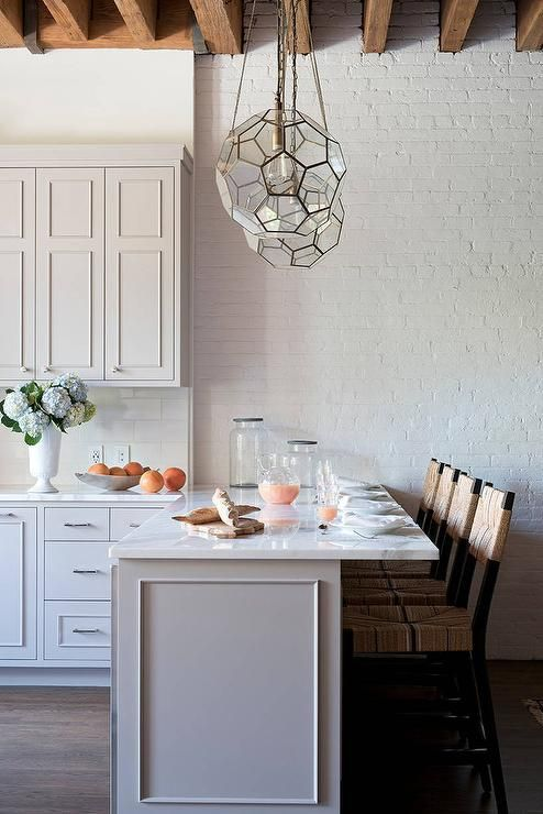 Four seagrass counter stools are positioned in front of a white marble countertop accenting a gray peninsula illuminated by two Arteriors Beck Pendants hung from a wood beam ceiling.