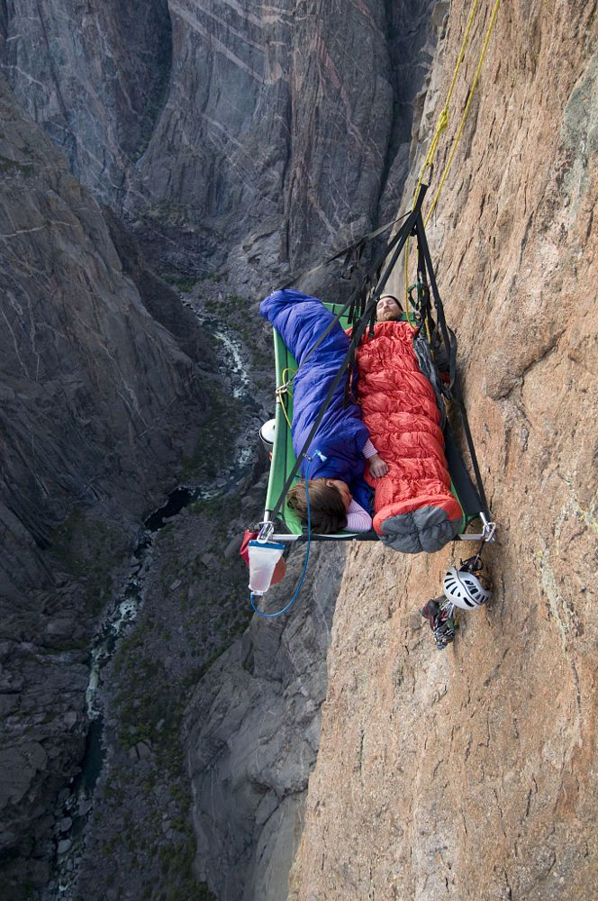 A man and woman sleep on portaledge while rock climbing a vertical face in Gunnison, Colorado. by Adventure Joe on 500px