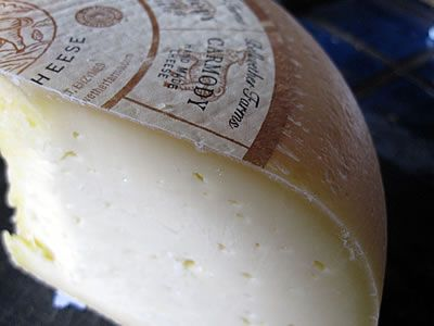 Just rub olive oil on the cut side of cheese to preserve it in an airtight container.  No plastic needed!
