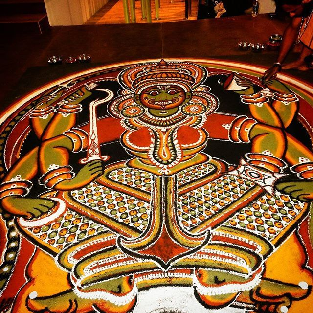 Kalamezhuthu is a ritual art form found in Kerala. While it is thought of to be similar to other forms like Rangoli, Kolam etc. it is not entirely so.  A form of temple art also done in sacred groves, Kalamezhuthu is normally done to worship goddesses ( Devi), serpents (Naga) and Lord Ayyappa (Sastha). Usually the ritual art is performed at the thresholds. The ritual ends with the erasing of the Kalam called Kalamazhkkal ( rubbing of the Kalam) and Nalikerameru ( breaking of coconut)…