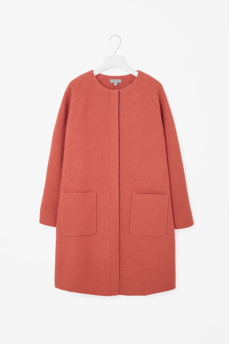 Made from boiled wool with a lightly textured feel and soft cotton lining, this collarless coat is a flared A-line shape. Slightly oversized, it has rounded raglan sleeves, a hidden front button fastening and two patch pockets on the front.