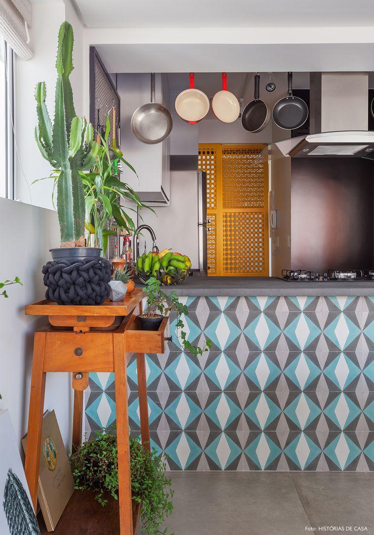 Cozinha tem bancada revestida com ladrilho hidráulico e, ao fundo porta amarela.