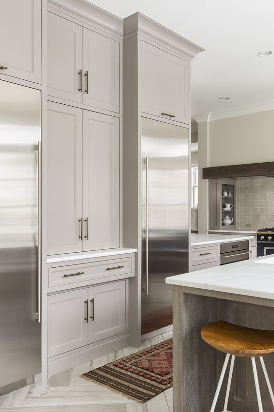 """Gorgeous! Softer white kitchen. Wall color: Benjamin Moore-Winds Breath; Ceiling color: Benjamin Moore-Simply White; Cabinet paint color: Farrow & Ball-Charleston Gray. Kitchen Hex pull: Ashley Norton, light bronze, 7-1/2"""" overall length. Note the cabinets to the left- bet they hold appliances. 100x48 Island: quarter sawn white oak w/ cerused finish; Bianco Lasa Oro marble   Kate Roos Design"""