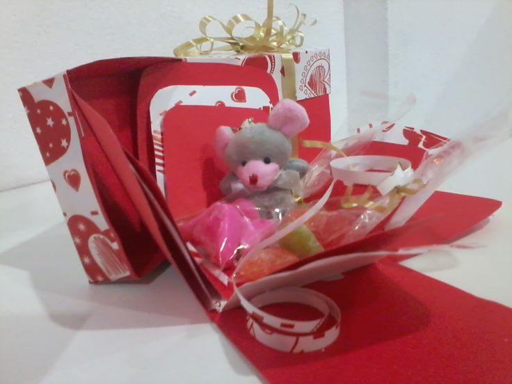 Caja pequeña de cartulina acompañada de golosinas y de muñeco de peluche pequeño.