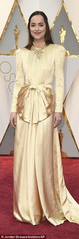 Golden girl: Decked in golden satin gown by Gucci, she was a dead ringer for the iconic award as she posed for snaps