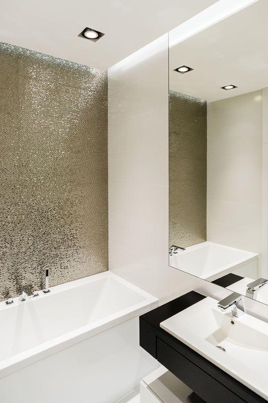 Złote kafle nad wanną nadają tej łazience ekskluzywny wygląd. Faktura na ich powierzchni, podświetlona listwą wbudowaną w szczelinę przy podwieszanym suficie, efektownie się mieni. Z kolorem złota elegancko komponuje się nowoczesna czarna szafka pod umywalką.