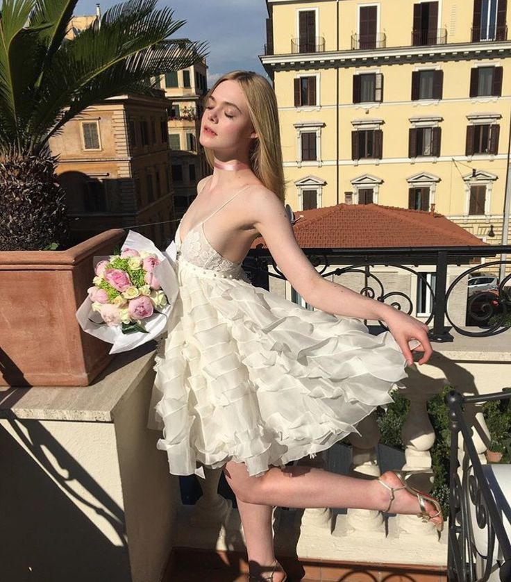 Elle Fanning in a white whimsical dress with a rose colored satin ribbon