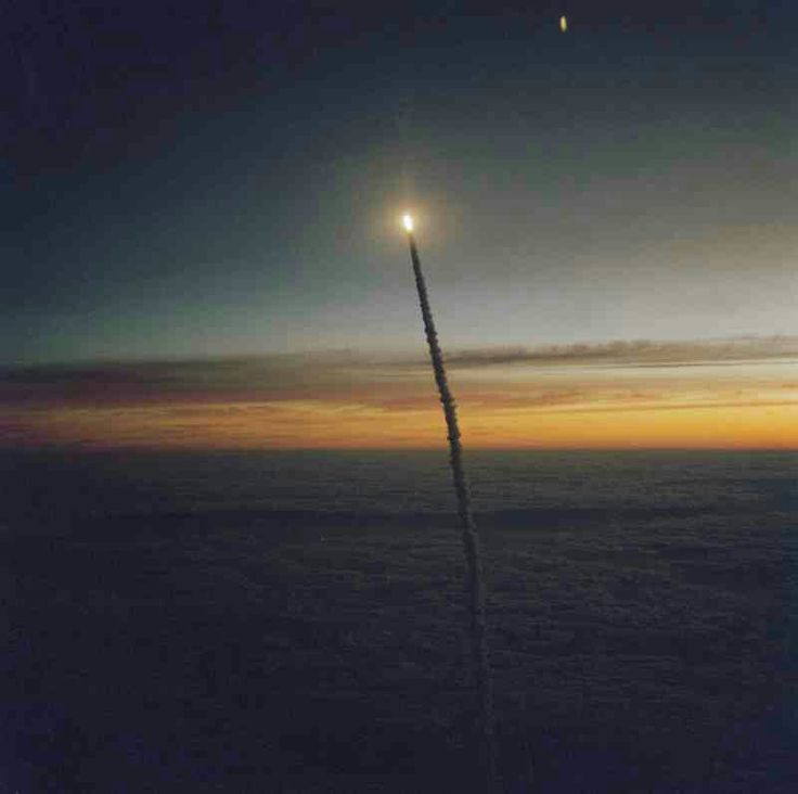 A Florida dawn scene on Oct. 5, 1984 forms the backdrop for the climbing Space Shuttle Challenger, its two solid rocket boosters and external fuel tank, launched on the eight-day STS-41G mission. The scene was photographed by astronaut Paul J. Weitz, who was piloting the Shuttle training aircraft (STA).  Crewed by Robert L. Crippen, Commander; Jon A. McBride, Pilot; Mission Specialists Kathryn D. Sullivan (now NOAA administrator), Sally K. Ride, David C. Leestma and Payload Specialists Marc…