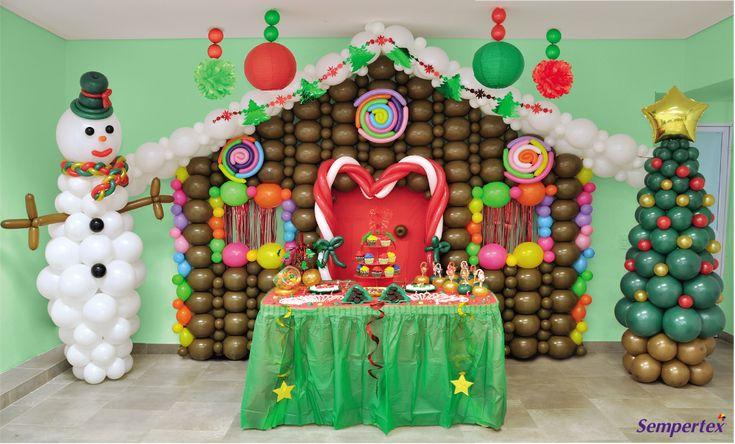 Como fondo de la mesa principal podemos apreciar una casa de dulces elaborada con globos LINK-OLOON® 12 Fashion Café con detalles coloridos de dulces elaborados con globos Verde Lima, Naranja, Fucsia, Azul Caribe, Lila y Amarillo. Para el techo utiliza globos LINK-O-LOON® 12 Fashion Blanco y coloca un festón metalizado como el que se aprecia en la foto.