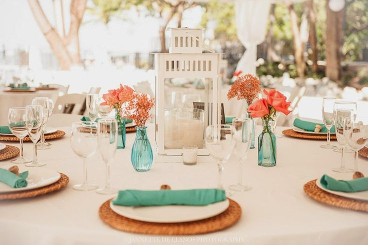 Reception centerpieces with coral and turquoise linens infusing vibrancy, fun and freshness at At Key Largo Lighthouse Beach Wedding Venue in the Florida Keys