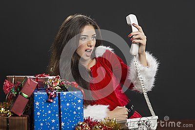 Young upset woman Santa helper holding up the telephone receiver and shouting in anger over dark background. A bunch of Christmas presents on table.  Download Christmas Time Crisis Royalty Free Stock Photo for free or as low as 0.68 lei. New users enjoy 60% OFF. 20,104,562 high-resolution stock photos and vector illustrations. Image: 35187655