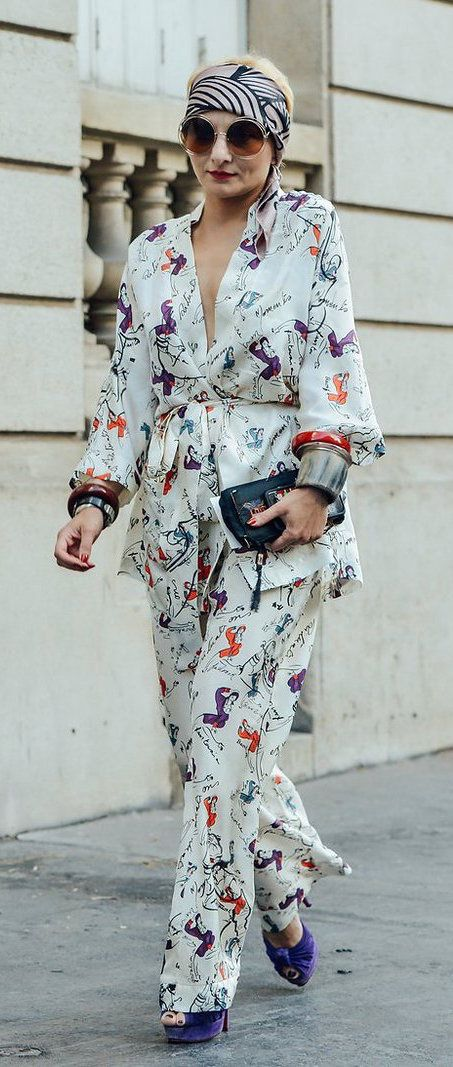 Stylist Catherine Baba in a printed silk ensemble with a head scarf and her classic round sunglasses