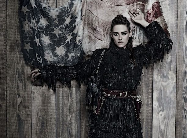 Who What Wear Blog Kristen Stewart Metiers D'Arts Paris Dallas Pre Fall 2014 Campaign Photographer Karl Lagerfeld Western Inspired Cowgirl Looks Style Corn Rows Hair SMokey Winged Eyes Beauty Fringe Leather Tiered Dress Jacker Studded Leather Belt Classic Chain Strap Bag
