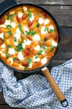 """Gnocchi mit Tomatensoße und Mozzarella   Madame Cuisine Rezept 1 Packung Gnocchi aus dem Kühlregal (ca. 400g) 1 EL Olivenöl 2 kleine Schalotten 1 Zehe Knoblauch 1 EL Tomatenmark Salz, Pfeffer, Muskatnuss 1 Dose stückige Tomaten (400g) 150g Kirschtomaten (am besten die kleinen länglichen """"Datteltomaten"""") 2 EL Weißweinessig 50ml Sahne 1 Bund Basilikum 1 Kugel Büffelmozzarella Chiliflocken nach Belieben"""