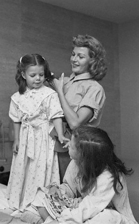 Rita Hayworth gets her daughters Yasmin and Rebecca ready for bedtime.