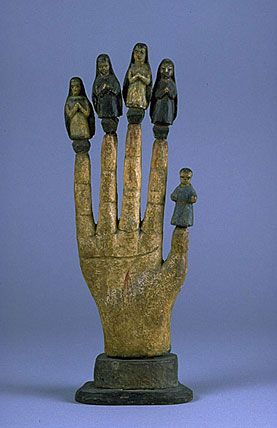 The Mano Poderosa or All-Powerful Hand, from the late 1800s, is a  Catholic version of its Roman predecessor. The 5 small figures atop the fingers are: Baby Jesus on the thumb; St. Joseph on the index finger; Virgin Mary on the middle finger; St. Joachim (Mary's father) on the 4th finger; & St. Anne (Mary's mother) on the pinkie.