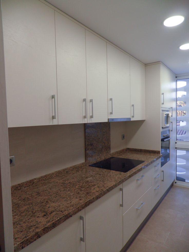 Como obtener una cocina luminosa, sin estridencias y con un elegante contraste: Pared Tau Cerámica Porcelánico rectificado Kemberg, mobiliario de laminado estructurado blanco roto de veta horizontal y encimeras en granito Juparana Carioca