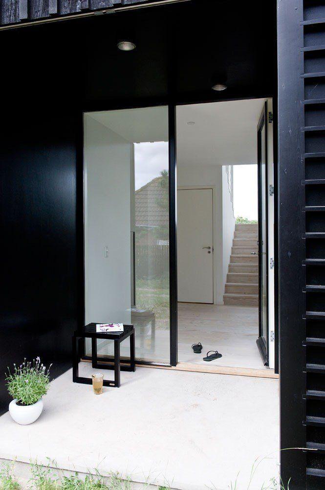 Hoveddøren er bygget som en karnap der kan lukkes helt til med høje skodder på skydefod