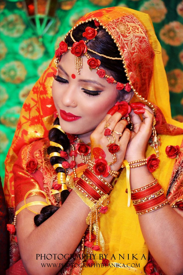 A beautiful Bengali bride on her Holud night. The traditional colors of yellow are worn, along with paper flower jewelry.
