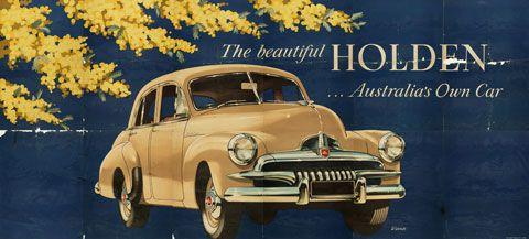 Billboard poster featuring a cream-coloured FJ Holden car in the centre and sprays of wattle in the top left corner. The text reads 'The bea...