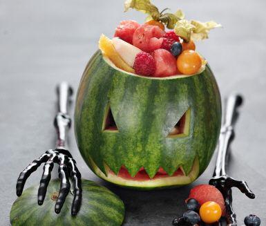 Möt Halloween med en läskig och läskande fruktsallad! Gröp ur en vattenmelon och skär ut ögon och mun. Fyll sedan vattenmelonen med melonbitar, physalis, färska hallon, blåbär, bitar av apelsin, äpple, päron eller något annat fruktigt. Nu har du en dessert som är skrämmande nyttig!