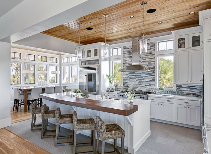 Gorgeous, light filled modern traditional kitchen design. White countertops, gray mosaic backsplash, white cabinets, butcher block island, wood ceilings and floors. So stylish, functional and cozy!