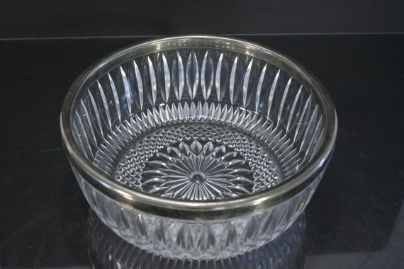 This large serving #bowl is #cut #glass with a silver-plate rim that features a…