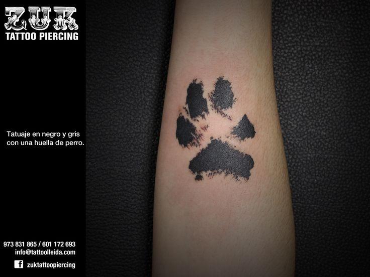Tatuaje en negro y gris con una huella de perro.