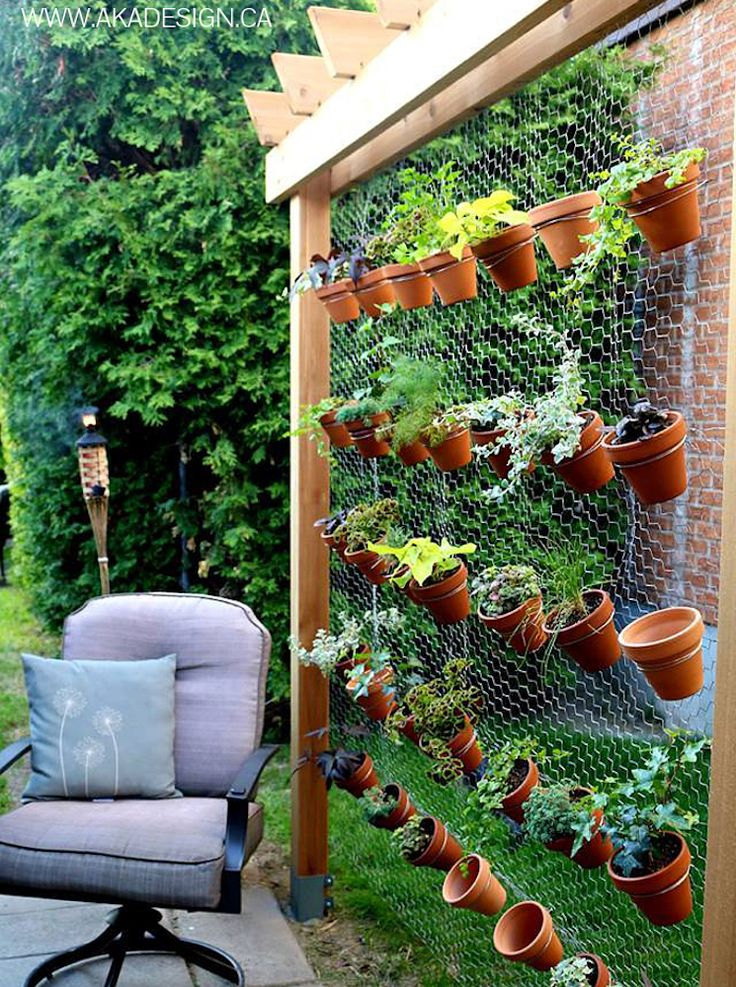 "DIY vertical garden with hex wire and terra cotta pots. Make tri-fold frame to loosely ""wrap"" around Magnolia tree."